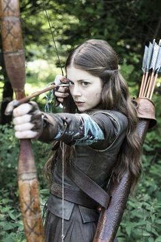 You are walking in the woods when this young woman suddenly steps out, aiming an arrow at you. You recognize her from wanted posters around the kingdom, but you don't know what she's wanted for. What do you do? (medieval)