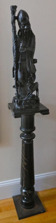 Striking Chinese carved figure with custom pedestal.
