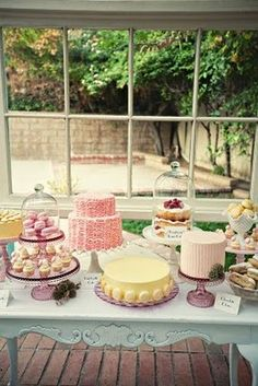 Dessert Table-double tiered cake stand.  Baby shoes on top tier, cup cakes on bottom tier.