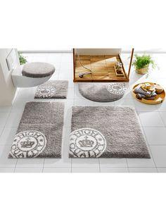 Lichtgrijze badmat met een witte ronde decoratie.