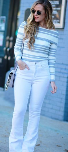 Casual winter white outfit styled with grey and white striped off the shoulder sweater, white high waisted flared jeans, Chloe Fay dupe bag, and gold choker