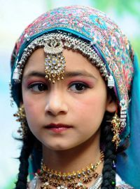 A schoolgirl, wearing a traditional Kashmiri outfit, waits for the arrival of Tibetan spiritual leader, the Dalai Lama prior to a function at the Tibetan school in downtown Srinagar on July 14, 2012. TOPSHOTS/AFP PHOTO/