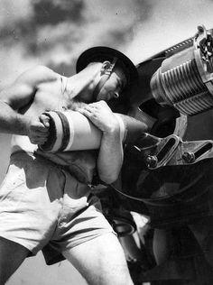 """Australian soldier loading a 6"""" field gun, World War II"""