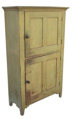 Z77 Early 19th century two door Storage Cupboard, from Lehigh Valley, Pennsylvania with old yellow paint over the original green, interior is a fantastic soldier blue, dovetailed case, molded cornice, doors are all full mortised and pegged.Nice high Lehigh Valley cut out foot,  one board construction  circa 1800 -1820