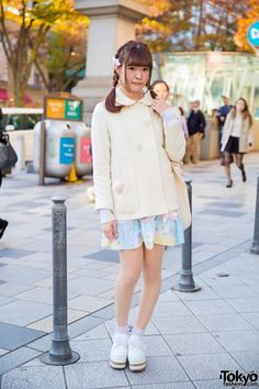 Dec 2014: Sa-yan is wearing a coat from the Harajuku brand Milk (with spades, hearts, diamonds, and clubs buttons) over a Nile Perch dress, pastel socks, and white creepers with cork soles and ribbon laces. Her unicorn tote bag is also from Nile Perch.