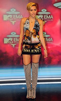 Miley Cyrus in knee high-boots and a dress with the faces of Biggie Smalls and Tupac at the MTV EMAs.