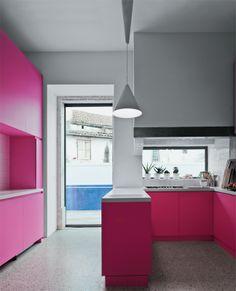 Na cozinha, a cor rosa sugere o lado feminino da casa. o mobiliário é de MDF e as bancadas brancas, de Corian (DuPont). Já para o piso escolheu-se granilite, em padronagem tradicional. A porta e a imensa janela toda envidraçada garantem muita luminosidade e reforçam a ligação com o pátio, onde se situa a piscina.