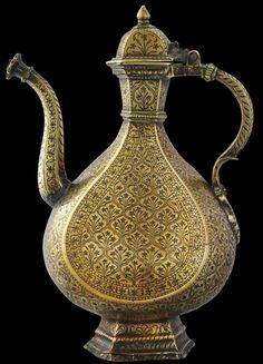 Mughal Brass Ewer, Engraved & with Dark Lac Inlay Northern India (probably Lahore) mid 17th to early 18th century  height:  34.5cm, weight: 1,835g  This magnificent Mughal brass ewer (aftaba) is of impressive size and refined proportions. It is in excellent condition for its age, has a warm, honeyed patina  and somewhat unusually for a North Indian ewer of this type and age, retains its original hinged lid.
