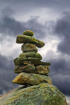 The direction of arms or legs could indicate direction for navigation, valley for passage.  an inukshuk without arms or with antlers added to it, would serve as a symbol for a store of food.