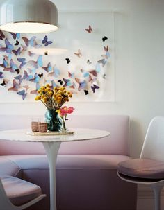 In an apartment designed by Celerie Kemble and Anna Burke, custom butterfly art hangs above a kitchen banquette. The iridescence of the butt...