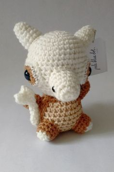 Cubone is ground-type Pokemon who wears a skull on his head based on his tragic origin story. He stands 6 inches tall and is made out of 100% acrylic yarn and 100% polyester fiberfill.      Pale Blue Dot Crochet (palebluedotcrochet.com)