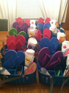 """Spa Party Favors: A showers caddy stuffed with: Flip Flops, Personalized Hand Towels, Eye Mask, """"spa water"""", Headband, Hair ties, and some candy."""