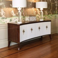 """Global Views  Mid-century modern style captivates on the Global Views Klismos media cabinet. Opening to reveal ample storage, four white doors surprise with golden starburst hardware.  70""""W x 21""""D x 31""""H  Walnut  4 adjustable interior shelves  Brass hardware"""