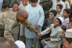 "U.S. Army Capt. Derrick W. Dew plays with young residents of the ""Old Corps"" area of Kandahar City, Afghanistan, June 8, 2011, during a ribbon-cutting ceremony for a new soccer field. Dew is commander of the 4th Infantry Division's 202nd Military Police Company assigned to the 1st Brigade Combat Team. The new field was one of many projects headed by Dew's unit and their Afghan National Security Forces partners in efforts to improve the city's quality of life, safety and security Sgt. Breanne…"