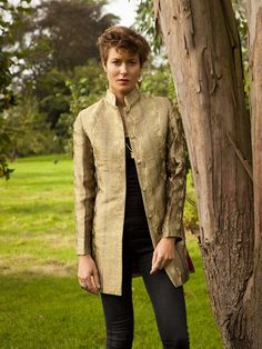 A ladies elegant jacket with the classic Nehru style collar.  Very simple and stylish.  No pockets or belts, just a simple cut.  Comes just below the bottom line.  Very popular. With vents at the side.  This Antique Gold silk embroidered jacket looks great worn with trousers. Length 31 inches / 79cm.  Embroidered Silk  Shown here in Antique Gold. Click the 'select a different fabric' option for more fabric choices.