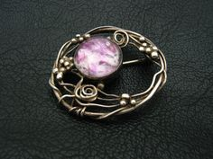 Mary Thew. Scottish Arts and Crafts brooch with maker's mark.  No mentions of materials (assume is silver and cabochon amethyst). Sold on eBay October 2013, £330. View 1.