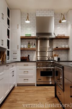 White cabinets, black countertops, white subway tiles, open wooden shelving, stainless steel appliances