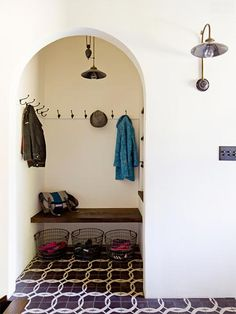 An industrial pulley pendant and wall hooks in the same finish keep everyday essentials within reach in this charming arched mudroom nook from Jessica Helgerson Interior Design.