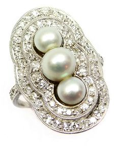Early 20th century three stone pearl and diamond cluster ring, c.1905   , the graduated pearls set vertically within a shaped double border of diamonds, millegrain set in platinum, diamonds to the shoulders. S.J. Phillips Ltd.