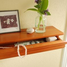 """The """"trim"""" on a floating wall shelf is actually a hidden drawer."""