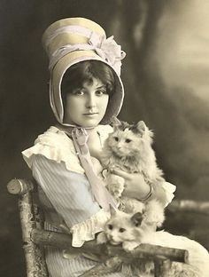 Girl in large bonnet, on a rustic chair, with two fluffy cats.