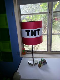 Minecraft TNT Lamp I used red card stock to wrap around a cylinder lamp shade then attached with double sided poster tape. I then  printed the TNT on regular printer paper and attached with more double sided poster tape.