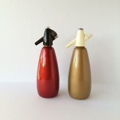 Choice of two vintage one-liter soda siphons made in England by BOC (Bins Oxygen Co., Ltd.). The bronze-color piece is older and was probably made in the 1960s or 1970s; the metallic red one probably dates from the 1970s or 1980s. The bodies are aluminum with plastic heads and appear complete with syphon head, plastic straw, washer, dust cap, and measuring tube; just needs a charger with holder. The measuring tubes are firmly in place and we did not attempt to remove them. They both measure…