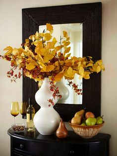 Welcome guests to holiday gatherings with a beautifully decorated entry table.Here golden gingko and bittersweet branches in a large sculptural vase, pears piled in a rustic stoneware bowl, a ready bottle of wine and low dish of nuts are all reminders of the harvest.