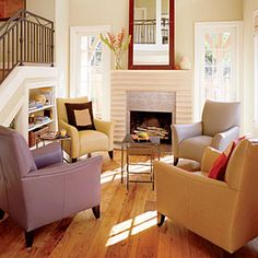 In the living room, a bright red mirror hangs above a cast concrete fireplace. There are four light-colored, leather arm chairs surround stacked coffee tables that are in front of the fireplace. Fireplace Windows, Small Fireplace, Concrete Fireplace, Fireplace Candles, Fireplace Seating, Fireplace Outdoor, Shiplap Fireplace, Freestanding Fireplace, Limestone Fireplace