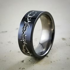 Black titanium with natural titanium Thorn carvings. We can engrave almost anything onto most of our rings. Don't see what your looking for? Just ask :-)