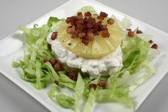 Det hakkede salat lægges som en bund på en lille tallerken. En ananasring ligges og fyldes med kyllingesalat. Endnu en ring ligges på. Pyntes med den den sprødstegte bacon, tomater og karse.