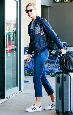 Karlie Kloss wears cropped denim overalls, a navy bomber jacket, and Adidas sneakers.