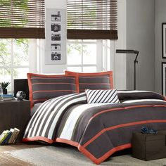 The Ashton Comforter Set provides style and simplicity through the use of basic colors and stripes. The face of the comforter uses white, olive green, orange and grey stripes in a variety of widths while the sham pulls the grey as the background and the orange into slimmer stripes for a dramatic look. A grey and white diagonal striped decorative pillow completes the look of this set.
