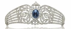 Centering upon a collet-set cabochon sapphire in a rose and old-cut diamond scrolling frame, extending tapered openwork diamond-set branches, 1910s