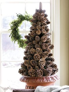 "Pinecone Tree: Create a pinecone tree on a cone-shaped foam base. Anchor the base in a container, then wire the cones onto 2"" wooden floral picks. Insert picks downward into the foam, starting at the bottom with the largest cones and working to the top with the smaller ones. Conceal the foam by tucking sheet moss among the pinecones."