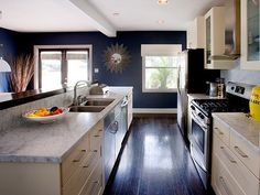 Deep blue with those dark floors, cream cabinets, grey marble, and stainless steel