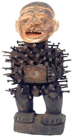 """Wooden Nkongi Fetish Statue.  The entire torso is embedded with nails, the face is covered with painted features, the eyes are made from inlayed pieces of glass, the phallus is visible and the hands hold a fetish cavity box. A piece of glass covers the opening of the cavity on this statue.         Late 1800's  15"""" x 6"""""""