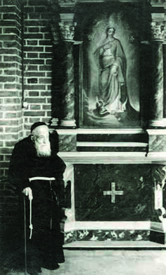 Father Leopold in front of a small altar in the cloister
