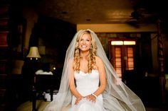 bride with curled down hair and a long veil. source:SMP
