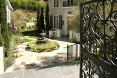 Gorgeous courtyard design with a stunning iron gate and central fountain. - love the layered heights around the fountain...
