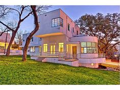 """The Art Moderne / Art Deco - Bohn House sits on a bluff above Shoal Creek with views of Pease Park, UT and downtown Austin. The home was designed by Herbert Bohn and was inspired by the 1937 film """"Lost Horizon"""" Features include a Magic Door made of Gum Wood that rises into the wall, Satin-Aluminium handrails studded with clear glass beads, original lighting fixtures, porthole windows,a sunroom, high celings in the living room."""