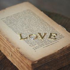 """リングを潜ませた おしゃれな""""LOVEメッセージ""""  LOVEの「O」部分に指輪を置いて、メッセージを作るキュートなアイデア。イニシャルプレートは東急ハンズや雑貨店などで購入を。プレートのメタル感は、リングのテイストに合わせて選ぶと◎。例えばつや消しのリングなら、くすみがかったアンティーク調の加工が施されたプレートなど。"""