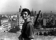 """Marina Ginestà.  """"Cuando en verano de 1936 posó orgullosa y desafiante en la terraza del Hotel Colón de Barcelona para Gutmann, ella tenía 17 años, un carné de las juventudes socialistas y el sueño de una revolución. Vestida con un uniforme miliciano, con el cabello al viento, pertrechada con un fusil que portó por primera y última vez en toda su vida, ella vivía un momento histórico, la primera victoria del pueblo en armas frente a los militares alzados contra la República""""."""