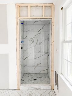 The best realistic looking marble effect herringbone tile and faux marble small shower renovation for a modern meets timeless bathroom.