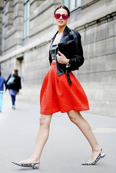 A bustier is paired with a leather jacket, bright red skirt, matching sunglasses, and printed slingback flats