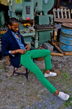 Green pants. Note the careful color blocking. White shoes, green plants, tonal blue shirt and sports coat. Part of the reason this works is because of the intense, saturated colors. Artfully done.
