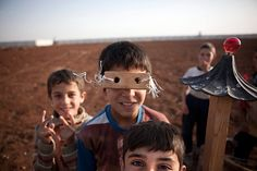 Azaz, Syria: Refugee children make toys from scrap materials found in a camp at the Turkish border