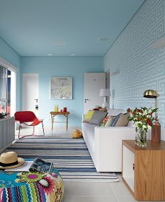 A parede na cor azul destaca o grafismo do adesivo branco, no projeto de Andrea Murao. O resultado parece papel de parede