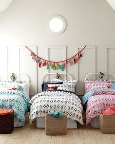 An adorable room for three with white bedframes, adorable penguin bedding and storage baskets at the end of each bed for those special items...