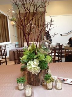 An arrangement of succulents & green flowers also using clear glass ornaments